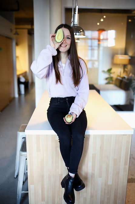 Woman holding half of avocado over her one eye