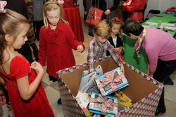 Children bring donated gifts at the M.D.Anderson Breakfast with Santa