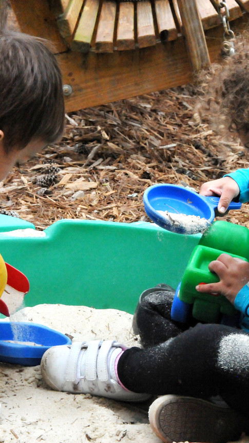 Little girl and little boy playing in a sandbox