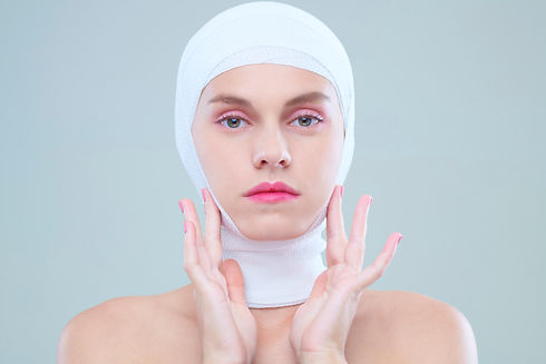 woman-touching-face-after-surgery-JKBS7C