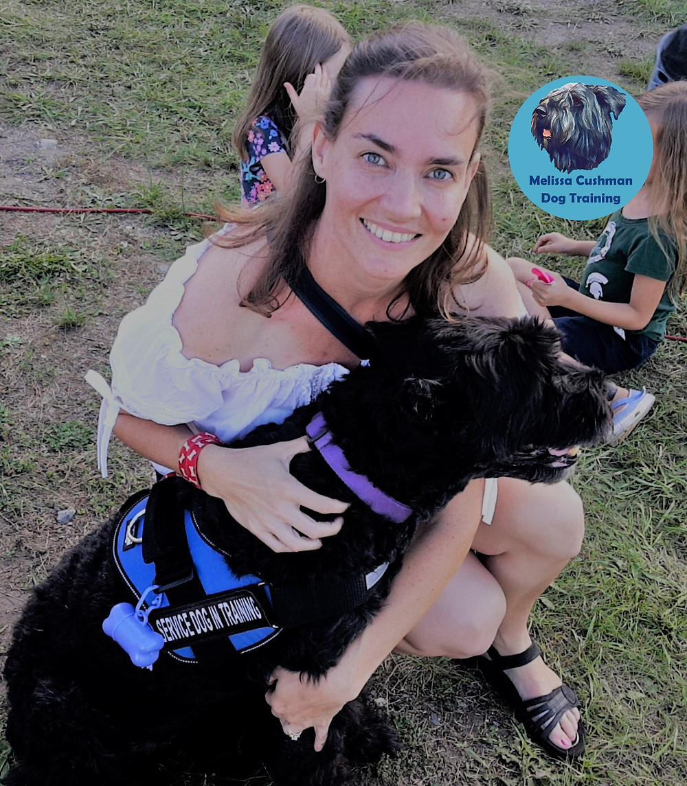 Melissa Cushman with Lilly a Bouvier Des Flandres a service dog in training sitting in the grass