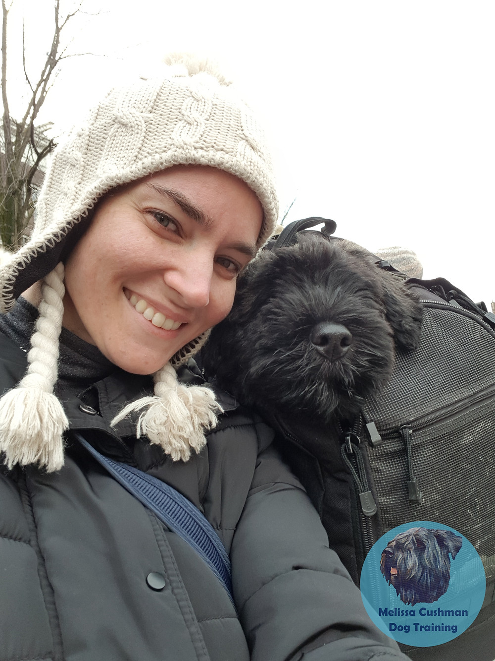 Melissa Cushman and Gunther a Bouvier des Flandres puppy are cuddled together Gunther is riding in a backpack.