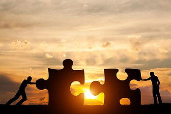 Two men connect two puzzle pieces. Sunse