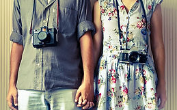 Couple holding hands with cameras hanging from their neck straps