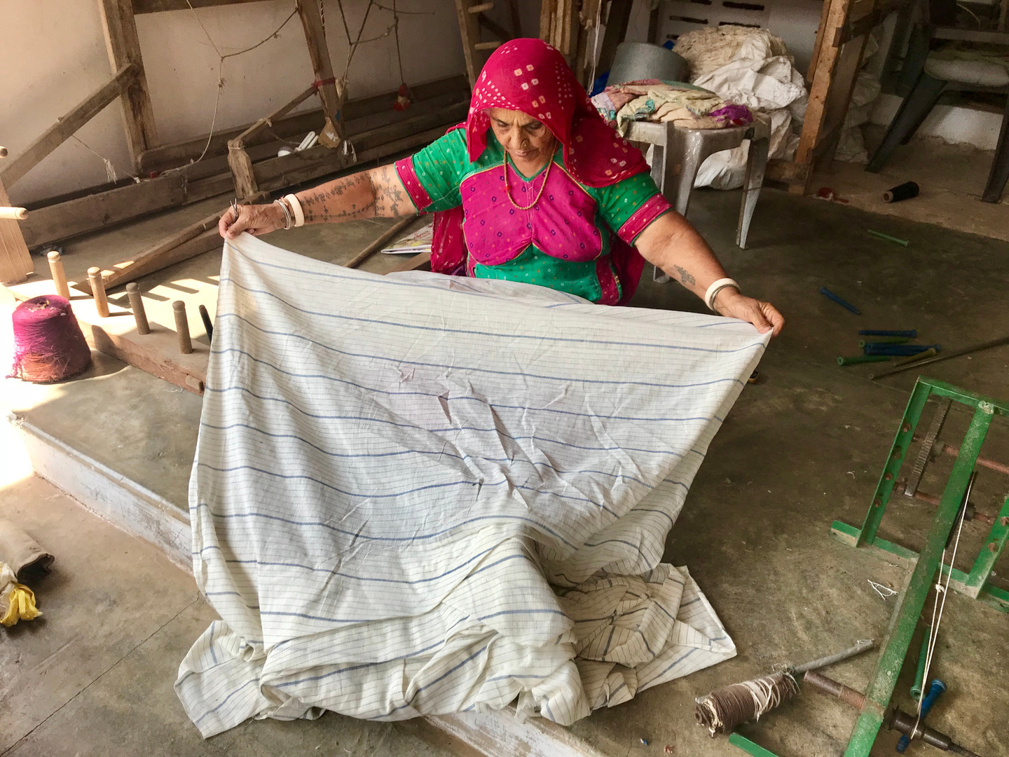 Grandmother finishing and snipping our cotton once its off the loom.