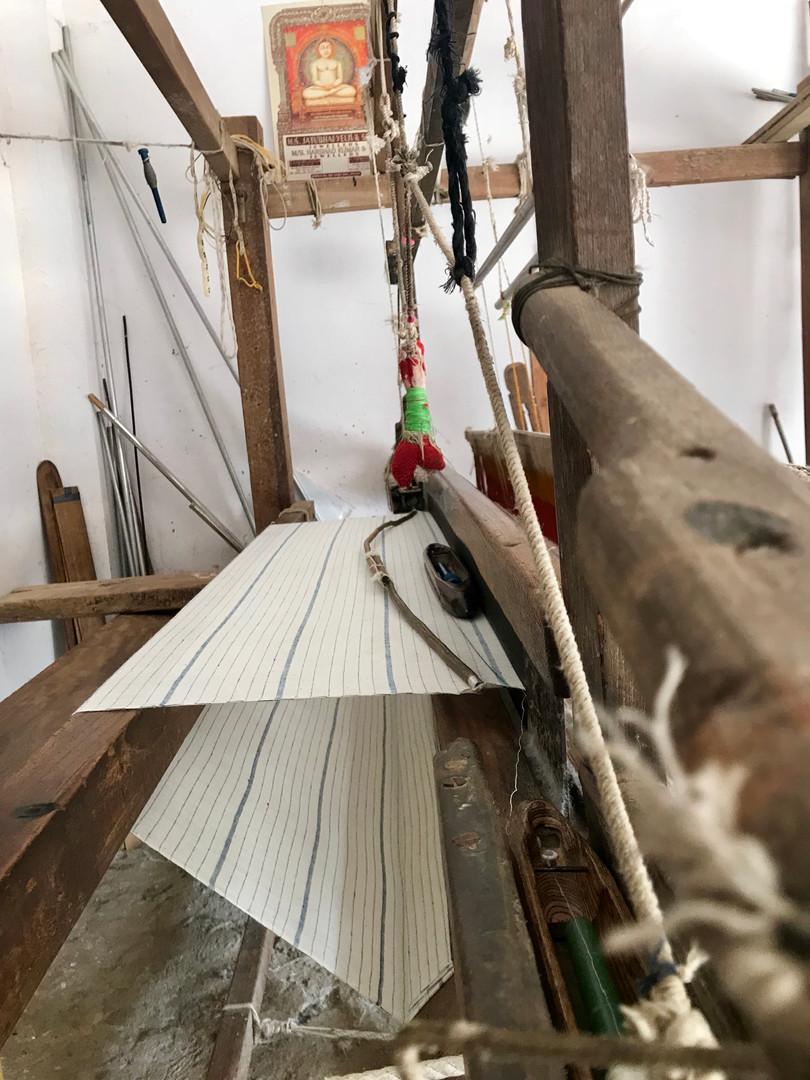 Some of our indigo striped organic kala cotton fabric on the loom.