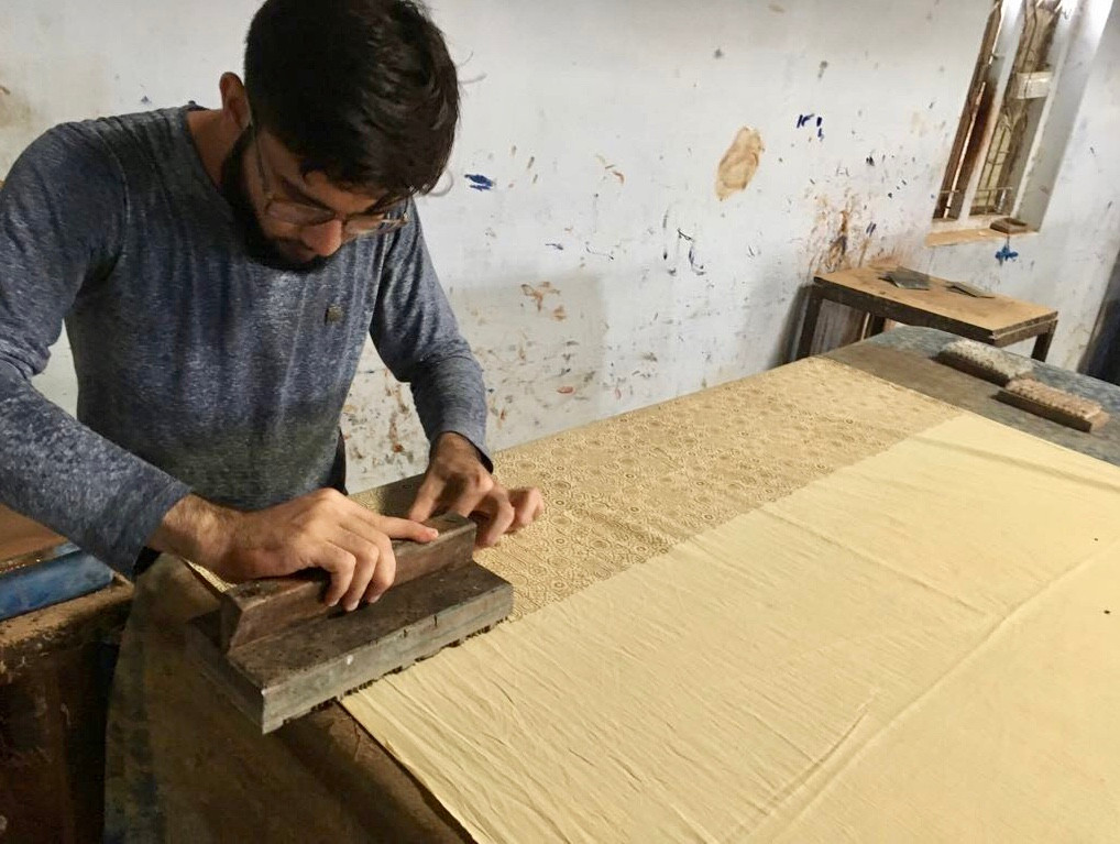 First layer of resist dye made of aribic gum and lyme being applied with hand carved printing block with the first layer of the pattern.
