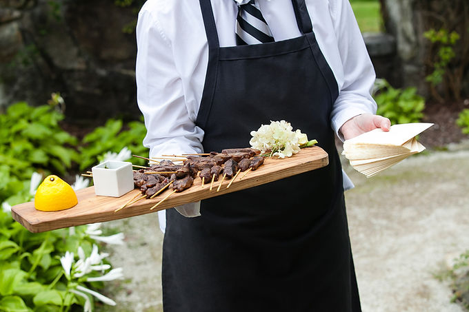 a server holding a wooden tray full of m