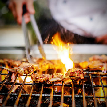 chef grilling lamb ribs on flame.jpg