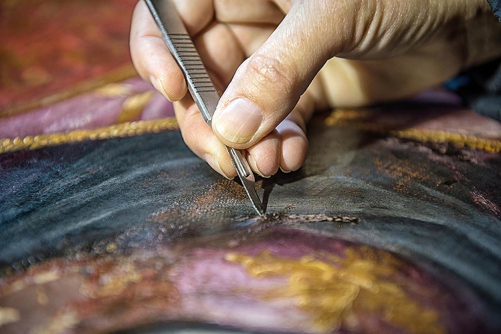 יד מחזיקה סכין ומגלפת בציור
