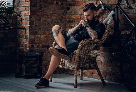 hipster tatuado sentado na cadeira