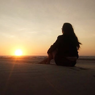 muler sentada na praia ao por do sol