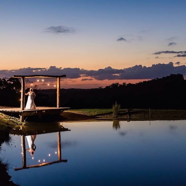 Scenery shot of bride overlooking lake at sunset