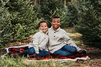 Two young Black boys  wearing white knit sweaters and sitting by a field of evergreen trees.