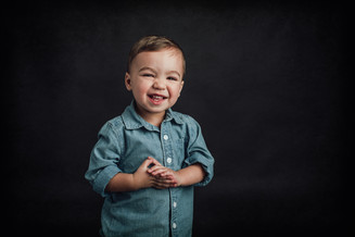 A chubby child laughing and holding hands against a dark background