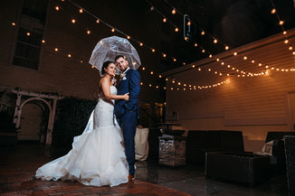 A bride and groom standing under outdoor fairy lights an umbrella on a rainy day