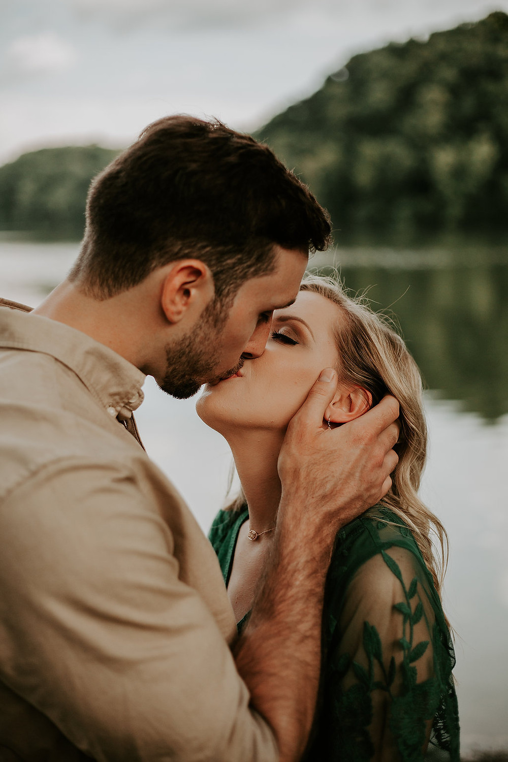 engagement session couple kissing by lake