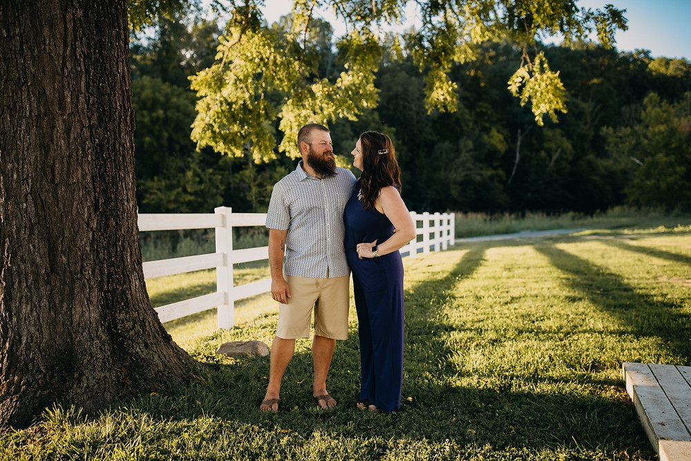 Couple smiling at each other during toddler siblings during Family of four walking and holding hands during Family session in Knoxville and Gatlinburg, TN during golden hour