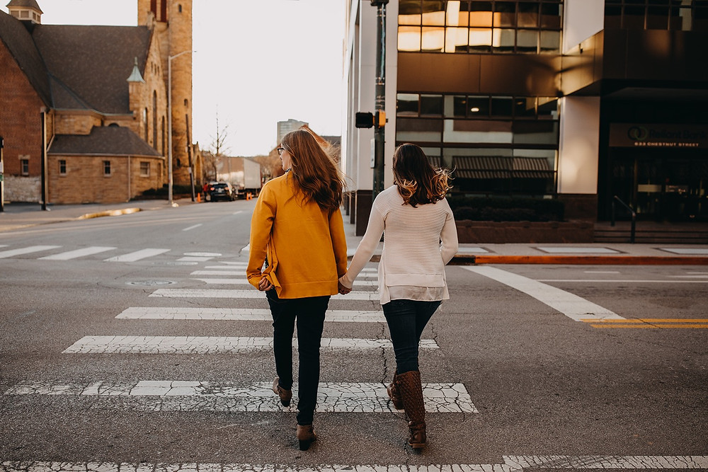 Same-sex couple crossing downtown urban street