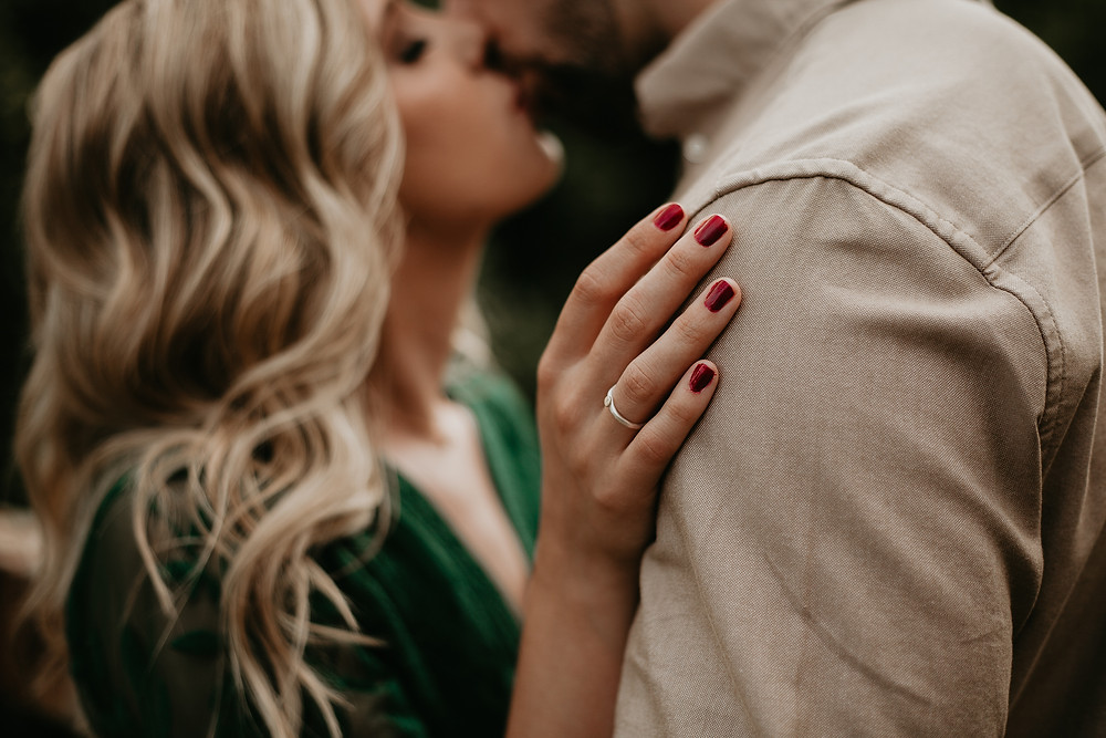 couple kissing with closeup of ring