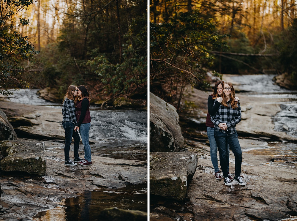 Same-sex couple cuddling by creek in nature