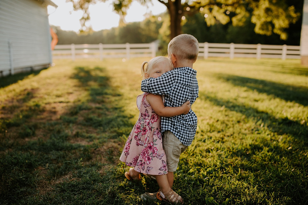 Toddler siblings hugging during Family session in Knoxville and Gatlinburg, TN during golden hour
