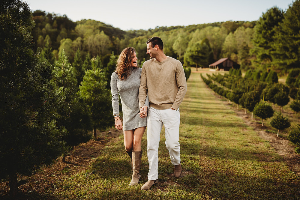 Couple walking and laughing through christmas tree farm