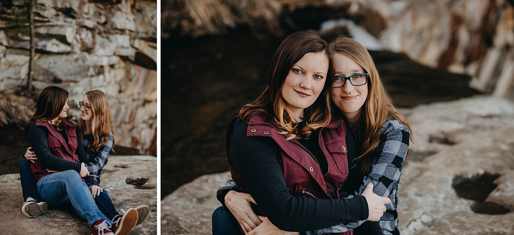 Same-sex couple cuddling on rocks next to mountain