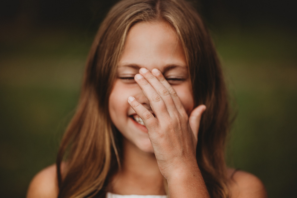 Portrait of a shy girl giggling