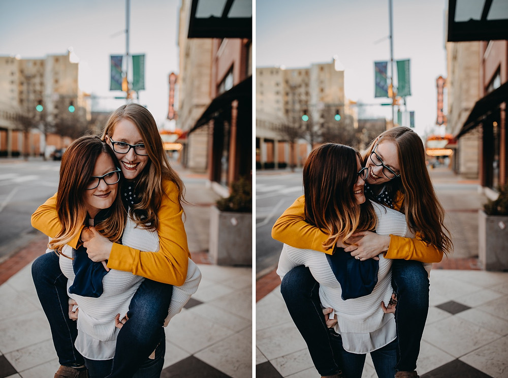 Same-sex couple giving piggyback ride and laughing downtown urban street