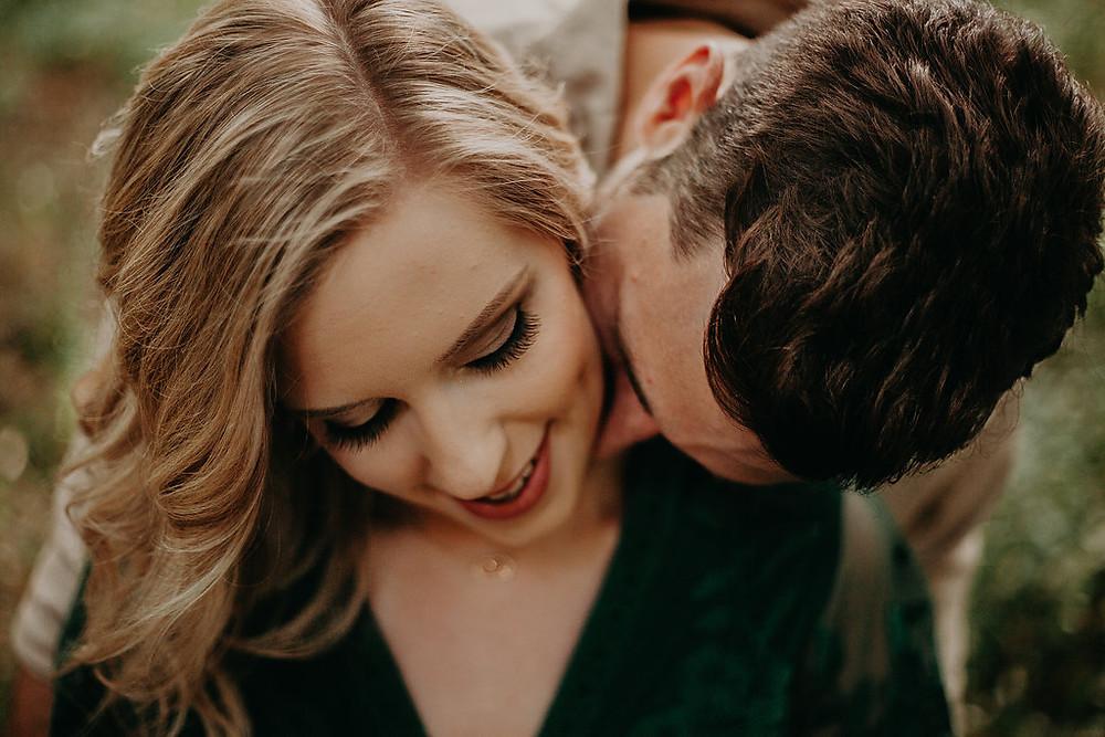 guy kissing girls neck during engagement session