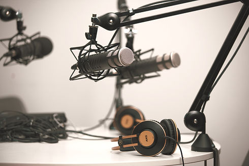 Three%20podcasting%20microphones%20on%20boom%20arms%20at%20a%20teble%20with%20headphones%20in%20shot