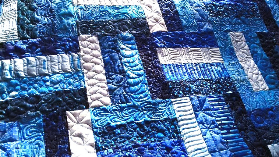 Patchwork quilt showing a variety of free motion quilting designs_edited.jpg