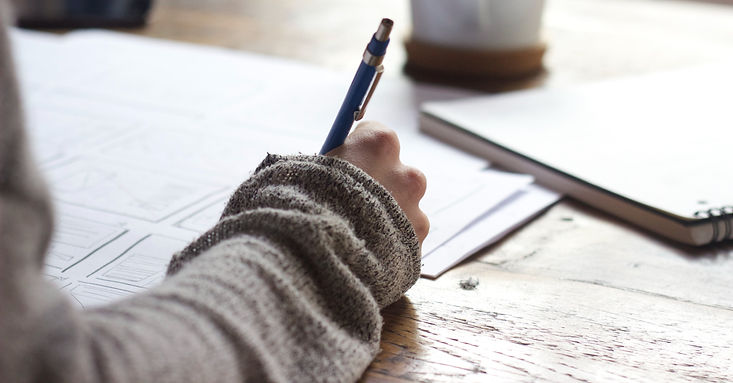 A photo that is zoomed in on a young woman's hand as she writes a letter on a wood desk in a cafe.
