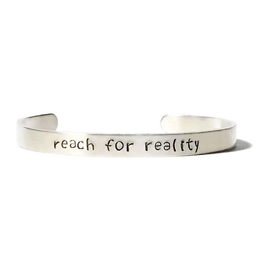 "Aluminum mantra bracelet hand stamped with ""reach for reality"" from Snarklets.net"