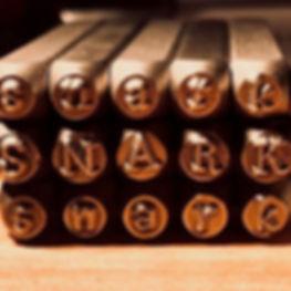 """Snarklets metal stamps spell """"snark"""""""