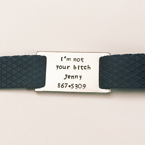 "Aluminum pet collar tag hand stamped with ""I'm not your bitch"" saying from Snarklets.net. Pictured on blue collar."