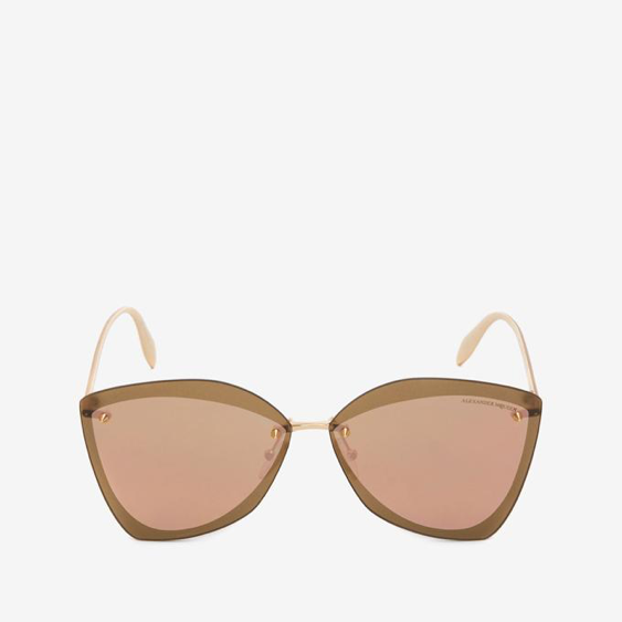 Modern shaped sunglasses with salmon colored lenses on a white background