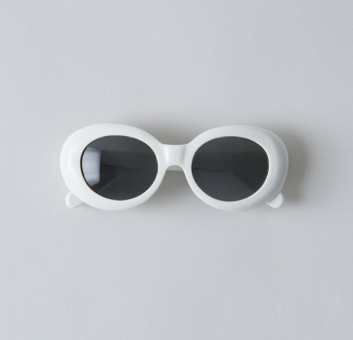 White framed sunglasses with black lenses on a grey background
