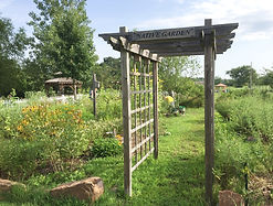 Rustic arbor leads to grassy path of Arkansas River Valley plants