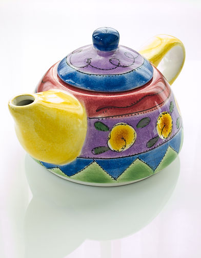 A colorful painting teapot on white tabl