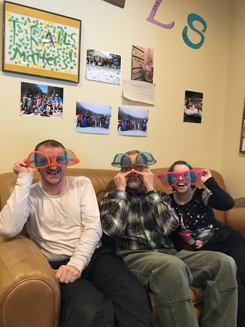 TRAILS Day Program Participants and a Volunteer laugh while wearing silly glasses.