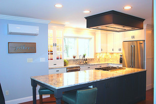 Kitchen By Ellen Lamoureaux, featuring dark blue cabinets in the center island, green leather chairs, and granite countertops with matching backsplash.