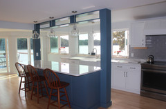 Kitchen designed by Nathan Johnson, waterfront in Portsmouth NH. Featuring a custom-built blue island structure, white showplace cabinetry, slate gray glass backspace, and quartz countertops.
