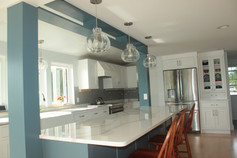Kitchen designed by Nathan Johnson, waterfront in Portsmouth NH. Featuring a custom-built blue island structure, white showplace cabinetry, slate gray glass backsplash, and quartz countertops.