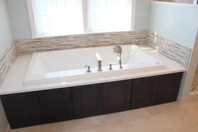 Berk Bathroom, designed by Patty Heath. Featuring a jacuzzi tub, encased in dark wood cabinet paneling. The backsplash is rough granite slivers.