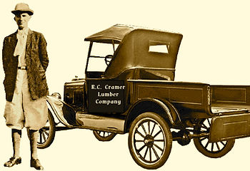 Image of Russell C. Cramer wearing knickers standing near model-T delivery truck.