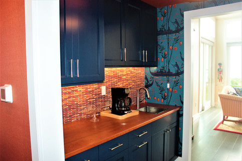 Breakfast nook designed by Patty Heath, featuring a wood countertop, dark blue cabinetry, and orange and red glass tile backsplash. Complimented by matching silk wallpaper.