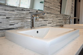 Berk Bathroom, designed by Patty Heath. Featuring a rough granite composite backsplash,  his and her sinks, satin nickel fixtures, and white quartz countertop.