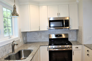 Granite countertops, and white cabinets in kitchen designed by Nathan Johnson.